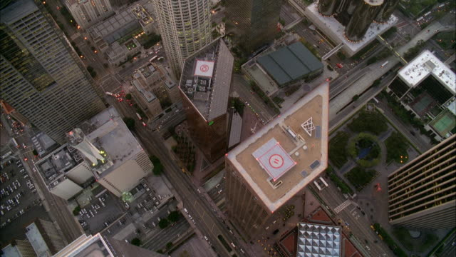 stockvideo's en b-roll-footage met aerial high angle down of roofs, rooftops, and heli-pads of downtown los angeles skyline. high rise buildings and skyscrapers visible. us bank tower. sunset. cars driving on city streets. - us bank tower