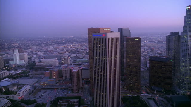 stockvideo's en b-roll-footage met aerial of downtown los angeles skyline. high rise buildings and skyscrapers visible. us bank tower. sunset. city hall visible. - us bank tower