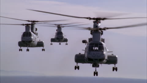 medium angle of three military chinook helicopters flying through air with ocean in bg. could be camp pendleton military base. could be army or marine helicopters. - army stock videos & royalty-free footage