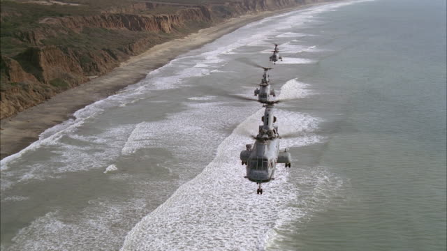 aerial of three military chinook helicopters flying over pacific ocean near cliff or bluff. could be camp pendleton area. beach or shore visible. - pazifikküste stock-videos und b-roll-filmmaterial