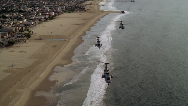 aerial of three military chinook helicopters flying over venice beach and moving north up pacific coast. helicopters fly over santa monica. landmark santa monica pier visible with roller coaster and ferris wheel. city visible in bg. piers. - venice beach stock videos & royalty-free footage