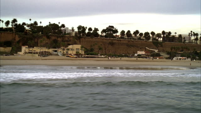 aerial of pacific coast highway near santa monica. beach and ocean visible in fg. cars driving on road in bg. cliff or bluff near highway. palm trees visible and apartment buildings, beach houses, and condominiums. lifeguard towers on beach. - pacific coast stock videos & royalty-free footage