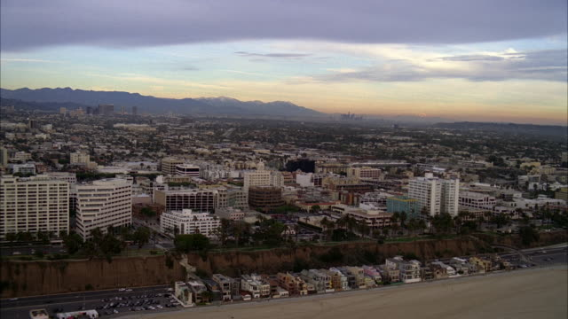 aerial of santa monica cliffs and bluffs near beach. city and mountains visible in bg. city skylines. apartment buildings, condominiums, and hotels visible. downtown los angeles skyline visible far in bg. - santa monica los angeles video stock e b–roll