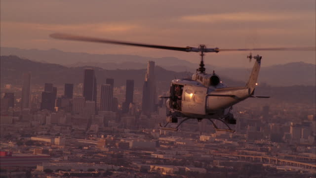 stockvideo's en b-roll-footage met aerial of uh-1n military helicopter flying towards downtown los angeles skyline. high rise buildings, skyscrapers, and office buildings visible. us bank tower. machine gun visible on helicopter. - us bank tower