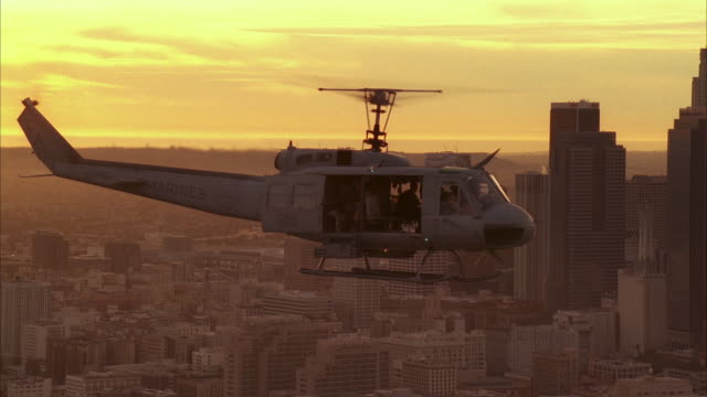 aerial of uh-1n military helicopter flying near downtown los angeles skyline. high rise buildings, skyscrapers, and office buildings visible. machine gun visible on helicopter. soldiers or marines partially visible. us bank tower visible. mountains visibl - us bank tower stock videos and b-roll footage