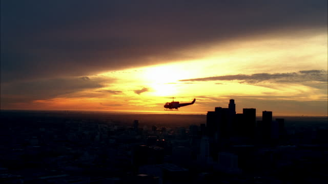 stockvideo's en b-roll-footage met aerial of uh-1n military helicopter flying near downtown los angeles skyline. high rise buildings, skyscrapers, and office buildings visible. machine gun visible on helicopter. soldiers or marines partially visible. us bank tower visible. - us bank tower
