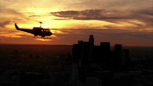 aerial of uh-1n military helicopter flying near downtown los angeles skyline. high rise buildings, skyscrapers, and office buildings visible. machine gun visible on helicopter. soldiers or marines partially visible. us bank tower visible. - us bank tower stock videos & royalty-free footage
