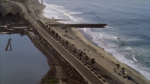 aerial over ocean or bay and cars driving on waterfront road. lifeguard station visible cars visible. palm trees. beach houses visible in bg. could be pacific coast highway. motorcyclist visible. - pazifikküste stock-videos und b-roll-filmmaterial