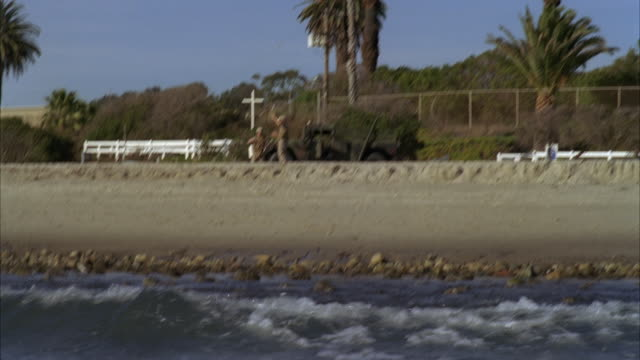 vídeos y material grabado en eventos de stock de wide angle of ocean and beach from surfer pov. palm trees and hill visible in bg. beach and sand visible from water. soldiers and hummer visible. soldier gesturing for swimmers or surfers to come into shore. amtrak train moves by in bg. - hummer