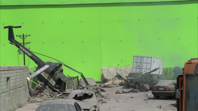 medium angle of debris, rubble, crashed cars and helicopter. small explosion, could be from bomb or grenade. could be war zone or during attack. green screen. destruction. ash. - rubble stock-videos und b-roll-filmmaterial