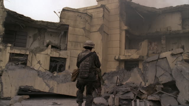 wide angle moving pov of destroyed multi-story building and rubble. could be war zone, bombing, terrorist attack, or natural disaster. smoke lingers in air. debris on street. two soldiers in camouflage run towards building with weapons. satellite dish on - army soldier stock videos & royalty-free footage
