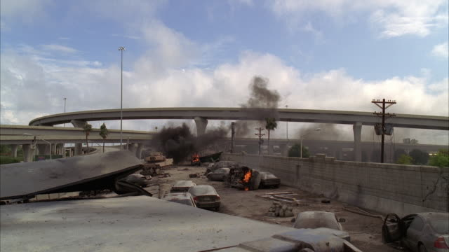 wide angle of freeway or highway with abandoned cars and suvs. overpasses visible in bg. debris and rubble visible. could be terrorist attack, bombing, disaster, or emergency. blue sky and cloud. overturned cars visible. fires and flames visible. explosio - rubble stock videos & royalty-free footage