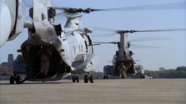 wide angle of four military chinook helicopters. could be military or army base. shed or hangar visible in bg. soldiers visible at back of helicopters. machine guns. - shed stock videos & royalty-free footage