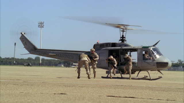 medium angle of uh-1n huey military helicopter landing on tarmac or runway of military or army base or airfield. soldiers in camouflage and duck. camera pans towards military jets. helicopters lands in bg. - army stock-videos und b-roll-filmmaterial