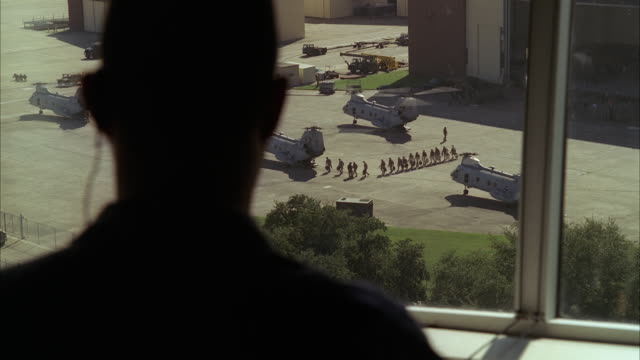 vidéos et rushes de high angle down from control room window of three chinook military helicopters, uh-1n huey, jets, and hummers or jeeps on tarmac or runway. could be military or army base or airfield. hangar partially visible in bg. military personnel walk around below. s - armée américaine
