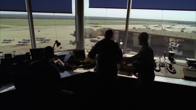 wide angle of control room window overlooking military airfield. three chinook military helicopters, jets, uh-1n huey, and hummers or jeeps on tarmac or runway. could be military or army base or airfield. hangar partially visible in bg. military personnel - binoculars stock videos & royalty-free footage