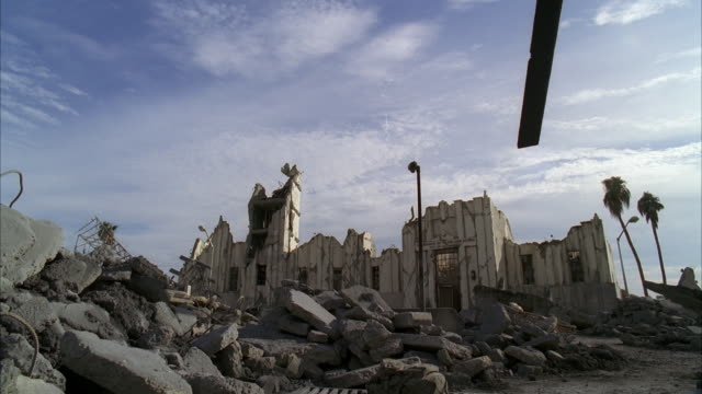 wide angle of destroyed building surrounded by debris and rubble. concrete and cement pieces mixed with metal. palm trees visible. street lights visible. piece of metal juts out in fg. could be terrorist attack or disaster. - rubble stock videos & royalty-free footage