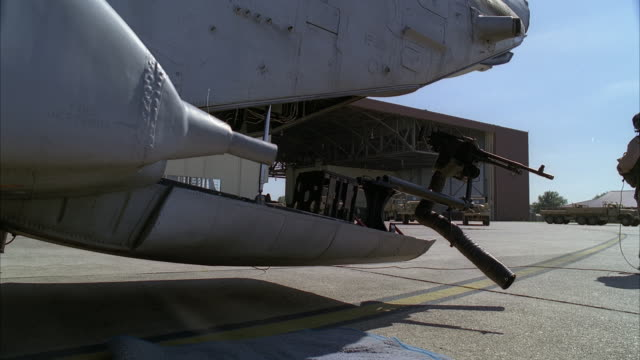 medium angle of cargo door of military helicopter or airplane. pilot or soldier with helmet visible in fg. soldiers running towards helicopter or plane in bg from hangar. military vehicles visible on tarmac or runway. machine gun attached to cargo door. c - army helmet stock videos & royalty-free footage