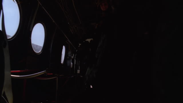 medium angle of soldiers filing into cargo area of chinook military helicopter or military airplane. windows visible. could be military base, army base, or airfield. - military stock videos & royalty-free footage