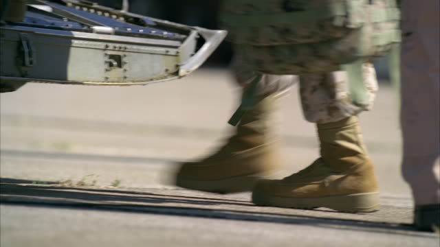 medium angle of soldiers with camouflage stepping up onto helicopter cargo area. gunner next to machine gun visible. could be chinook military helicopter. could be military or army base. hangar visible in bg. - army soldier stock videos & royalty-free footage
