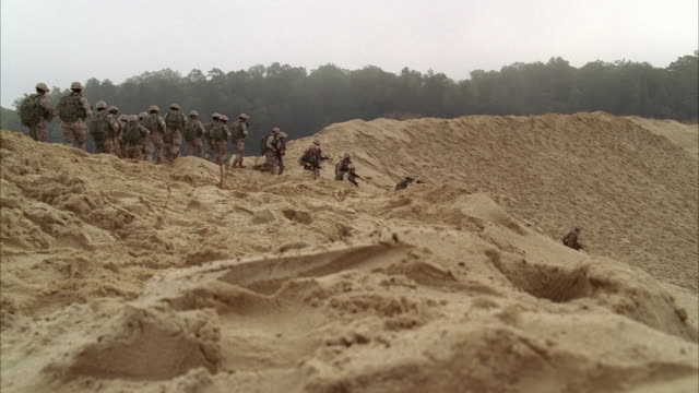 wide angle of soldiers in camouflage carrying backpacks running along beach or sand. men run towards military truck and hummer. could be training. trees visible in bg. - soldat stock-videos und b-roll-filmmaterial