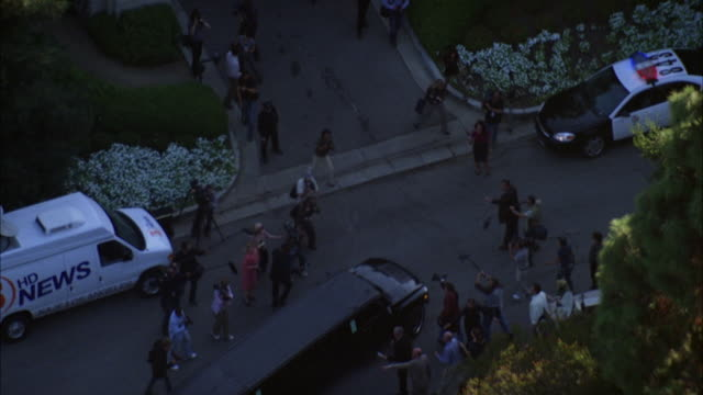 aerial of upper class mansion or estate. reporters, news vans, and police cars parked in front of gate to house. manicured shrubbery visible. could be beverly hills. camera men and reporters follows bus or hummer limo into driveway. fountain visible. ambu - hummer stock videos and b-roll footage