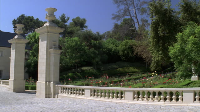 pan right to left from gate or entrance to upper class house, mansion, or estate as maybach 62 v240 luxury car enters into driveway. trees, stone fence, and flowers visible. could be beverly hills. columns at entrance to house. car pulls into garage. - driveway stock videos & royalty-free footage