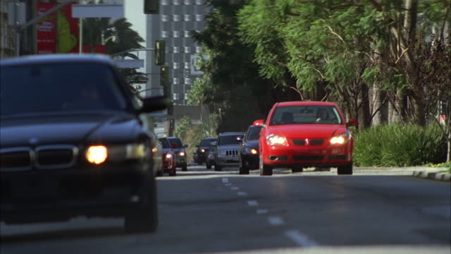 medium angle of cars or traffic on wilshire boulevard. man on motorcycle weaves through traffic. car stunts. - wilshire boulevard stock videos & royalty-free footage