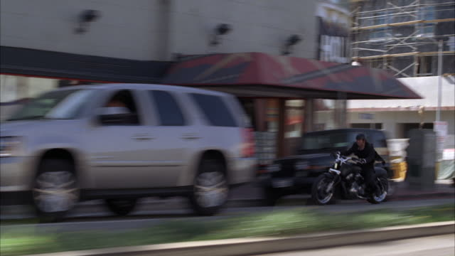 vídeos de stock e filmes b-roll de pan right to left of man on motorcycle weaving through cars and traffic on wilshire boulevard. shops, storefronts, and pedestrians visible. city streets. car stunts. - wilshire boulevard