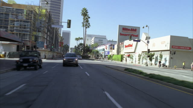 vídeos de stock e filmes b-roll de process plate straight back of wilshire boulevard in los angeles. high rise apartment buildings, businesses, grocery store, and shops visible lining street. trees. movie theater marquee. - wilshire boulevard