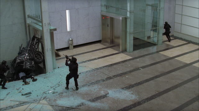 vídeos de stock e filmes b-roll de high angle down of office lobby. doorway with exit sign visible. marble entryway. could be bank or corporate building. flashing lights visible. could be fire drill or alarm. broken glass and crashed vehicle visible. swat team armed with weapons visible. c - escombros material
