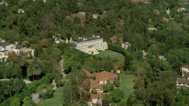 aerial of fleur de lys mansion or upper class house. two story stone building. trees and grass lawn. swimming pool. courtyard. residential area. los angeles area. - fleur de lys stock videos & royalty-free footage