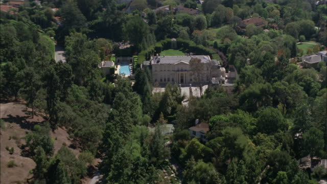 aerial of fleur de lys mansion or upper class house. two story stone building. trees and grass lawn. swimming pool. courtyard. residential area. city skyline in bg. los angeles area. - fleur de lys stock videos & royalty-free footage