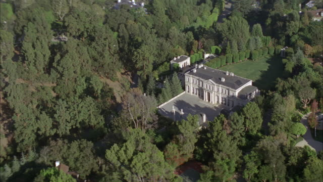 aerial of fleur de lys mansion or two story upper class house. stone building. grass lawn and swimming pool. trees. residential area. los angeles area. - fleur de lys stock videos & royalty-free footage