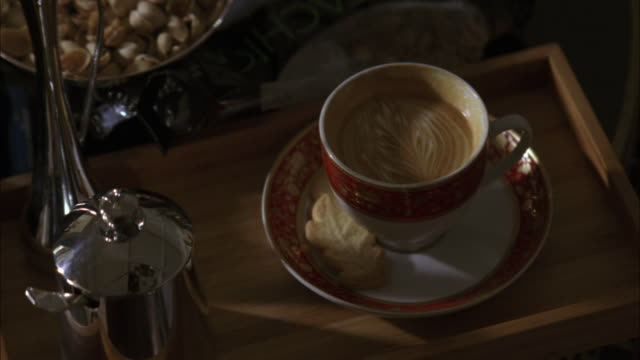 close angle of wooden tray with coffee, cappuccino or latte with leaf design in foamed milk. cookie on plate. pistachio nuts. food and drink. - coffee drink stock videos & royalty-free footage
