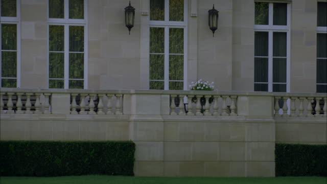 medium angle of fleur de lys mansion. stone building. upper class house. balcony, porch or patio. bushes or hedges. - fleur de lys stock videos & royalty-free footage