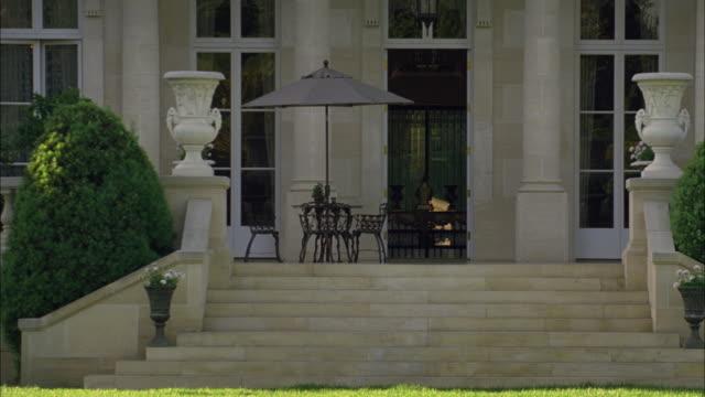 medium angle of fleur de lys mansion. stone building. upper class house. porch or patio. bushes or hedges. - fleur de lys stock videos & royalty-free footage