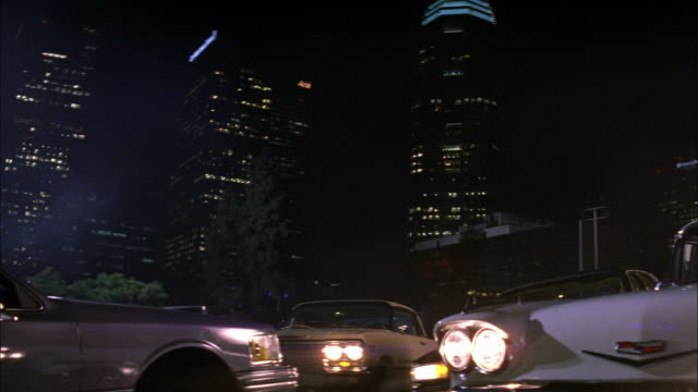 pan down los angeles city skyline. high rise office and apartment buildings. trees in fg. us bank tower. classic cars parked in lot in fg. could be car show. - us bank tower stock videos & royalty-free footage