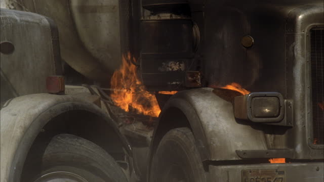 close angle of cement mixer truck on fire. flames visible near tires. truck begins to move. could be construction zone. - cement mixer stock videos & royalty-free footage