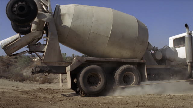 wide angle of cement mixer truck being pulled sideways towards camera. another partially visible trucks drives into fg. could be construction area or quarry. stunts. - cement mixer stock videos & royalty-free footage