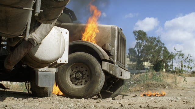 medium angle of cement mixer truck's tire on fire in construction area or quarry. additional cement mixer  truck is pushed toward truck on fire. - cement mixer stock videos & royalty-free footage