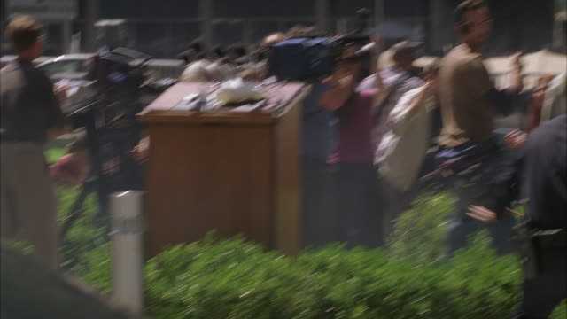 medium angle of reporters, journalists, or paparazzi standing and crouching in front of hotel or office building with cameras and microphones. could be attack on press conference. cars visible in bg. people running and panicking. police officers visible. - press conference stock videos and b-roll footage