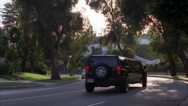 vídeos y material grabado en eventos de stock de wide angle of upper class residential street. could be westwood or beverly hills. hummer limo driving on street. neighborhoods. - westwood neighborhood los angeles