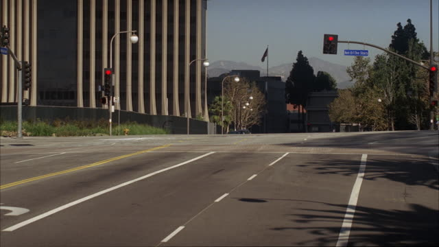 pan down from high angle down over avenue of the stars in century city. city streets. cars visible driving and stopped at intersection. - century city stock-videos und b-roll-filmmaterial