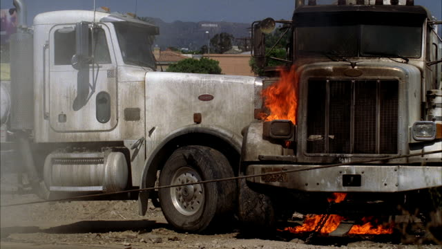 medium angle of two cement mixer trucks after collision. fires or flames and smoke visible. one truck swings around. car stunts. industrial area. - cement mixer stock videos & royalty-free footage