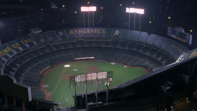 aerial pan around oakland-alameda county coliseum in oakland. stadium lights and baseball field visible. empty stands or bleachers visible. oakland athletics emblem visible on stadium. scoreboard visible. camera zooms into first base and dugouts. also kno - oakland verwaltungsbezirk alameda county stock-videos und b-roll-filmmaterial