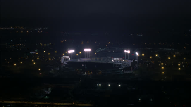 aerial pan around oakland-alameda county coliseum in oakland. stadium lights and baseball field visible. empty stands or bleachers visible. oakland athletics emblem visible on stadium. scoreboard visible. city skyline partially visible. oracle sports aren - oakland verwaltungsbezirk alameda county stock-videos und b-roll-filmmaterial