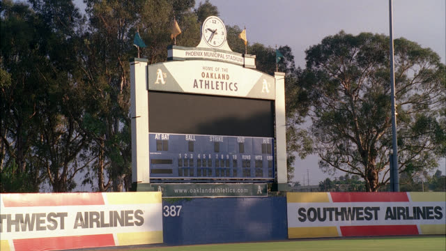 wide angle of oakland athletics scoreboard, phoenix municipal stadium, arizona. flags slowly waving and time clock visible on top of scoreboard. spring training baseball field. trees in bg. banner advertisement for southwest airlines visible. - spring training stock videos & royalty-free footage