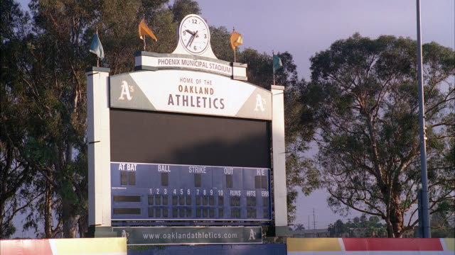 wide angle of oakland athletics scoreboard, phoenix municipal stadium, arizona. flags slowly waving and time clock visible on top of scoreboard. spring training baseball field. trees in bg. - spring training stock videos & royalty-free footage