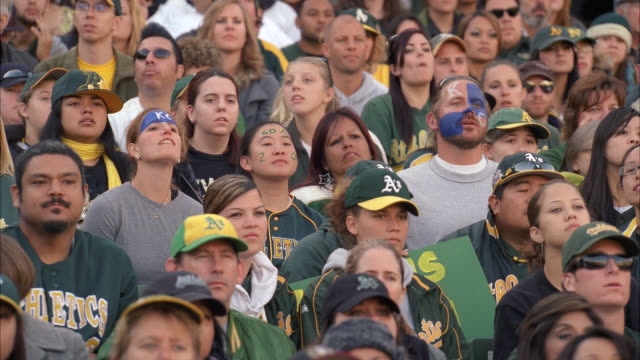 medium angle of oakland athletics baseball fans sitting in stadium stands. people wearing oakland 'a's' baseball caps, sweatshirts, t-shirts. fan for opposing team wear face paint with 'kc' stand up and applaud as others grimace and look disappointed. spo - anno 2002 video stock e b–roll